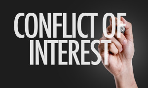 Hand writing the text: Conflict of Interest